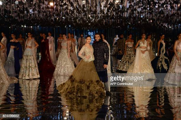 Indian bollywood actors Alia Bhat and Ranveer Singh along with other models present creations by Indian fashion designer Manish Malhotra during the...