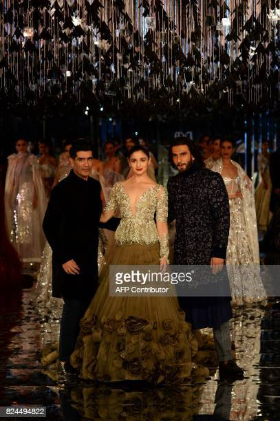 Indian bollywood actors Alia Bhat and Ranveer Singh present creations by Indian fashion designer Manish Malhotra during the FDCI India Couture week...