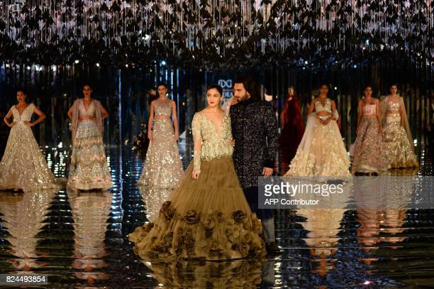 Indian bollywood actors Alia Bhat and Ranveer Singh presents creations by Indian fashion designer Manish Malhotra during the FDCI India Couture week...