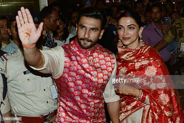 Indian Bollywood actors and recently-wedded couple Ranveer Singh and Deepika Padukone acknowledge fans gathered at the Mumbai international airport...