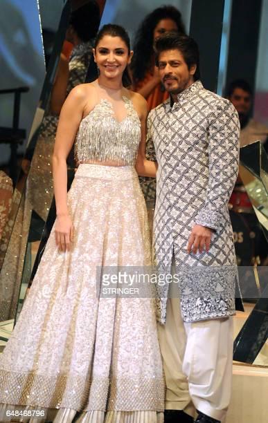 Indian Bollywood actors Anushka Sharma and Shah Rukh Khan showcase creations by designer Manish Malhotra at the fundraiser Mijwan 2017 fashion show...