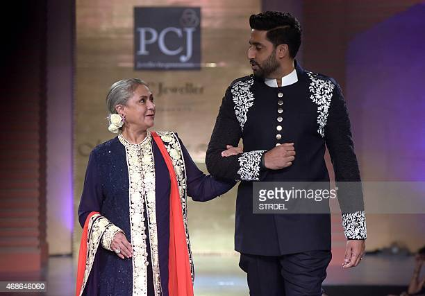 Indian Bollywood actors Jaya Bachchan and her son Abhishek Bachchan model creations by designer Manish Malhotra during a charity fashion show in...