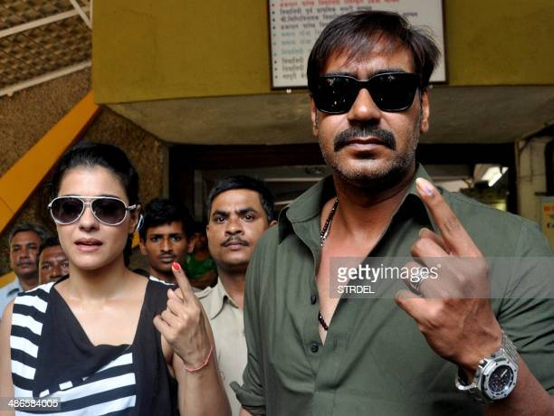 Indian Bollywood actors Kajol Devgn and Ajay Devgn pose for a photograph after voting at a polling station in Mumbai on April 24 2014 India's...