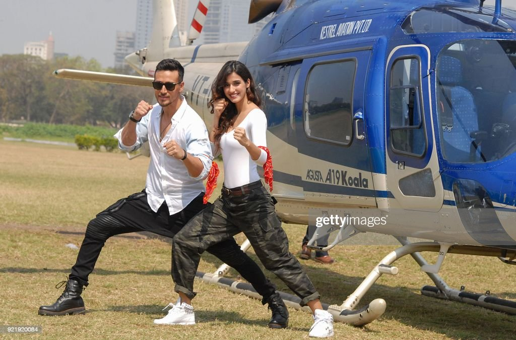 Indian Bollywood actors Tiger Shroff (L) and Disha Patani take part in a promotional event with a helicopter for their upcoming action Hindi film Baaghi 2 in Mumbai on February 21, 2018. /