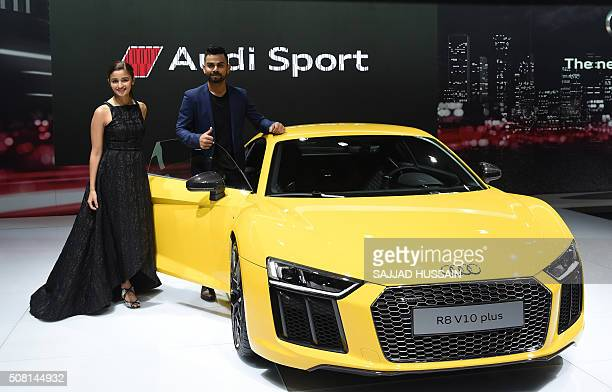 Indian Bollywood actress Alia Bhat along with Indian cricketer Virat Kohli pose with the newly launched Audi R8 V10 plus at the Indian Auto Expo 2016...