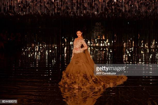 Indian bollywood actress Alia Bhat presents a creation by Indian fashion designer Manish Malhotra during the FDCI India Couture week 2017 in New...
