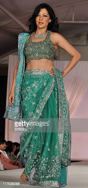 Indian Bollywood actress and model Aditi Govitrikar walks the ramp during a fashion show by designers Manish Malhotra and Shaina NC in support of...