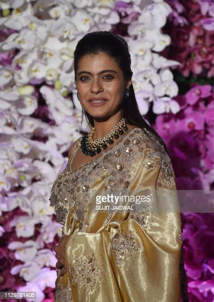 Indian Bollywood actress Kajol Devgn poses for photographs as she arrives to attend the wedding reception of Akash Ambani son of Indian businessman...