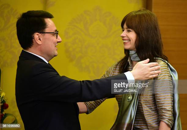 Indian Bollywood actress Kalki Koechlin greets France's ambassador to India Alexandre Ziegler at a ceremony to bestow Koechlin with the French...