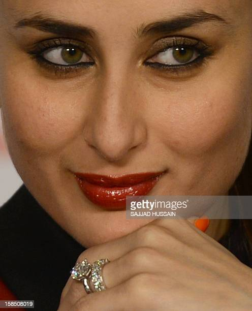 Indian Bollywood actress Kareena Kapoor Khan looks on while her engagement ring and wedding band are seen worn on her finger during a press...