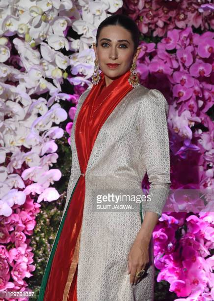 Indian Bollywood actress Karisma Kapoor poses for photographs as she arrives to attend the wedding reception of Akash Ambani, son of Indian...