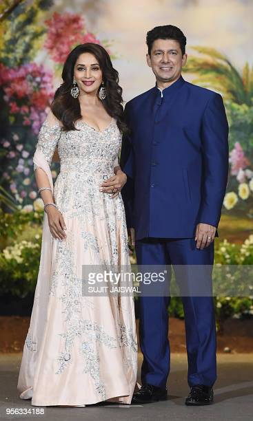 Indian Bollywood actress Madhuri Dixit and husband Shriram Nene pose for a picture during the wedding reception of actress Sonam Kapoor and...