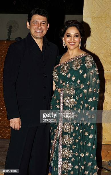 Indian Bollywood actress Madhuri Dixit Nene with her husband Shriram Madhav Nene attend the wedding reception of Bollywood film director Punit...