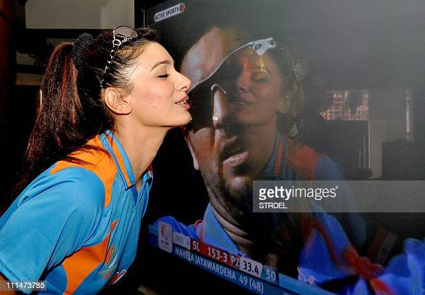 Indian Bollywood actress Mink Brar kisses a television screen showing an image of Indian cricketer Yuvraj Singh during the Cricket World Cup final...
