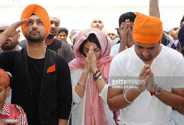 Indian Bollywood actress Neeru Bajwa with Punjabi actors Diljit Dosanjh and Gippy Grewal pay their respects during a visit to the Golden Temple in...