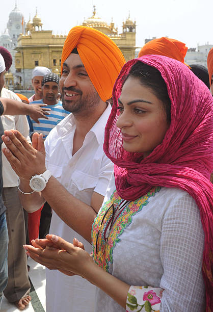 Indian Bollywood actress Neeru Bajwa with Punjabi singer and actor Diljit Dosanjh pose during a visit to the Golden Temple in Amritsar on June 19...