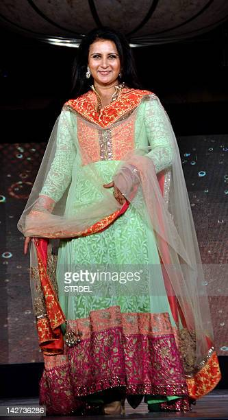 """Indian Bollywood actress Poonam Dhillon displays a creation by designer Manish Malhotra for a public awareness campaign """"Save and Empower the Girl..."""