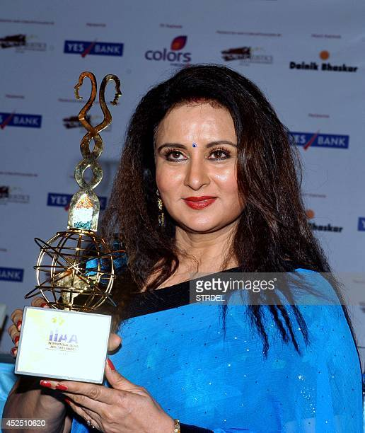 Indian Bollywood actress Poonam Dhillon poses with the 2014 International Indian Achievers Awards trophy during its unveiling in Mumbai on July 21...