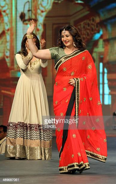 Indian Bollywood actress Poonam Dhillon waves after falling as she models clothing during a cancer fundraiser in Mumbai on May 11 2014 AFP PHOTO/STR