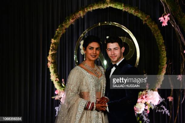 Indian Bollywood actress Priyanka Chopra and US musician Nick Jonas who were recently married pose for a photograph during a reception in New Delhi...