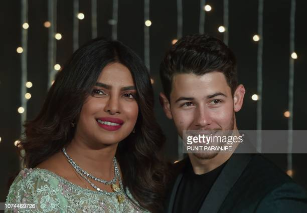 Indian Bollywood actress Priyanka Chopra and US musician Nick Jonas who were recently married pose for a picture during a reception in Mumbai India...