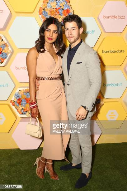 Indian Bollywood actress Priyanka Chopra with her husband US musician Nick Jonas pose for a picture at Bumble's launch party in New Delhi on December...