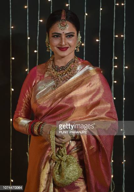 Indian Bollywood actress Rekha poses as she arrives to attend the wedding reception of a Bollywood actress in Mumbai, India, on December 20, 2018.