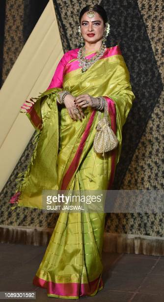 Indian Bollywood actress Rekha poses for a picture during the wedding reception of film producer Mukesh Bhatt's daughter Sakshi Bhatt in Mumbai late...