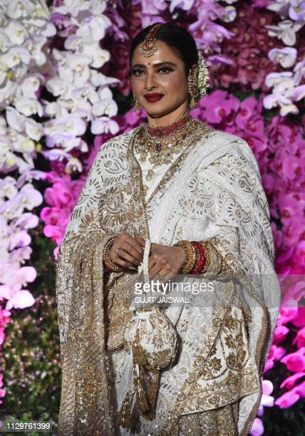 Indian Bollywood actress Rekha poses for photographs as she arrives to attend the wedding reception of Akash Ambani, son of Indian businessman Mukesh...