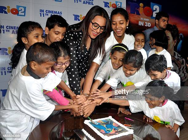 """Indian Bollywood actress Sonakshi Sinha cuts a cake with children as she attends a screening of the animated film """"Rio 2"""" in Mumbai on April 7, 2014...."""