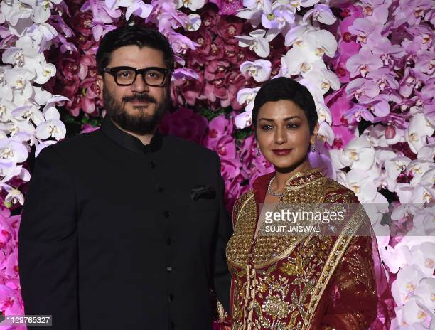 Indian Bollywood actress Sonali Bendre with her husband film director Goldie Behl poses for photographs as she arrives to attend the wedding...
