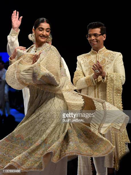 Indian Bollywood actress Sonam Kapoor and director Karan Johar display creations by designers Abu Jani and Sandeep Khosla during the 14th annual...