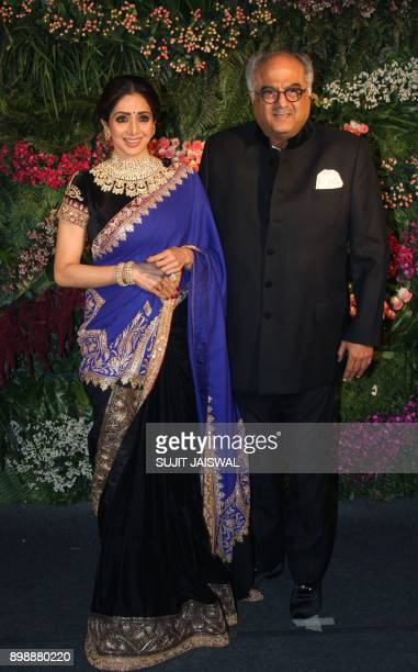 Indian Bollywood actress Sridevi and husband Boney Kapoor pose for a photograph during the wedding reception of the Bollywood actress Anushka Sharma...