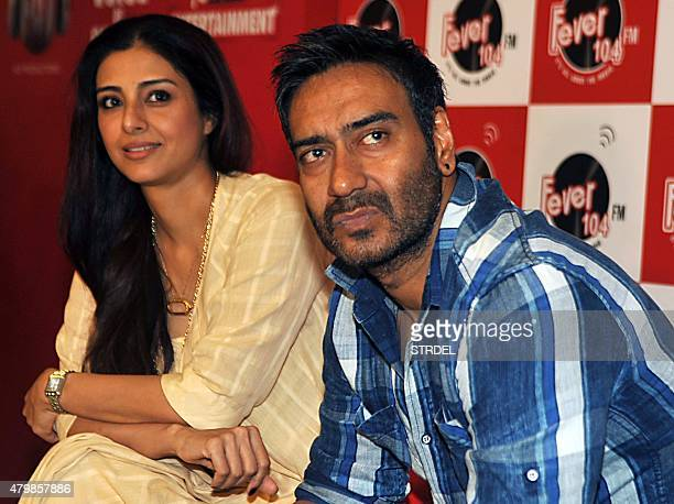 Indian Bollywood actress Tabu and actor Ajay Devgn pose as they take part in a promotional event visit to Fever 104 FM Studios ahead of the...