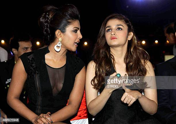 Indian Bollywood actresses Priyanka Chopra and Alia Bhatt speak as they attend the BIG STAR Entertainment Awards 2014 in Mumbai on December 18 2014...