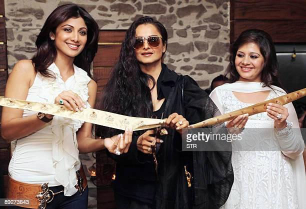Indian Bollywood actresses Shilpa Shetty , Rekha and Kiran Bawa cut the ribbon during the launch of Iosis MediSpa in Mumbai on July 26, 2009. AFP...