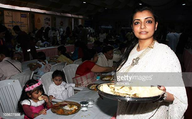 Indian Bollywood dance choreographer Vaibhavi Merchent serves blessed food during celebrations in Mumbai on the occasion of the Hindu festival of...