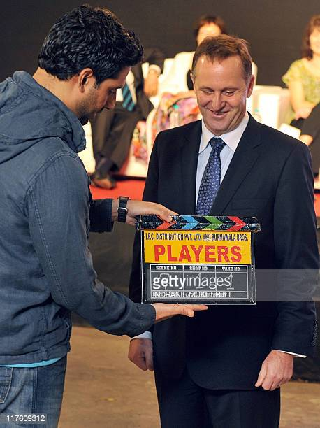 Indian Bollywood film actor Abhishek Bachchan demonstrates the use of a clapstick to New zealand Prime Minister John Key on the set of the movie...