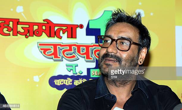 Indian Bollywood film actor Ajay Devgn as a brand ambassador for Hajmola Chatpata No1 poses during a promotional event in Mumbai on February 26 2015...