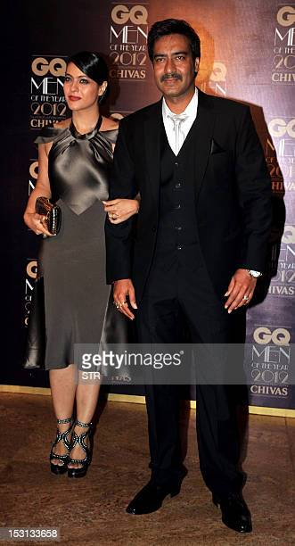 Indian Bollywood film actor Ajay Devgn with his wife Kajol holds his Cinematic Icon award during the 'GQ Men of the Year Awards 2012' in Mumbai on...