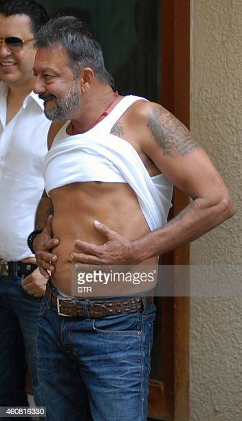 Indian Bollywood film actor Sanjay Dutt poses on his arrival at his residence Imperial Heights Pali Hill Bandra in Mumbai after being granted a 14day...