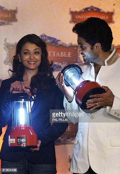 Indian Bollywood film actress Aishwarya Rai Bachchan and husband film actor Abhishek Bachchan pose with Solar Lanterns as they pledge their support...