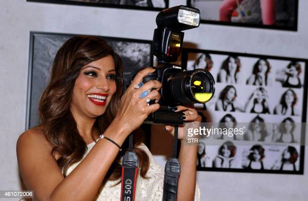 Indian Bollywood film actress Bipasha Basu poses with a photographer's camera during the launch of Daboo Ratnani's Celebrity Calendar 2015 in Mumbai...