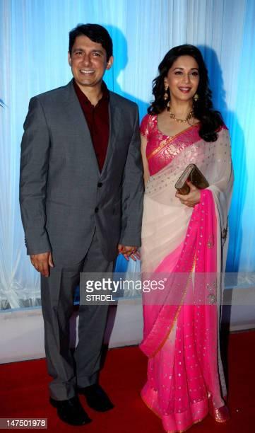 Indian Bollywood film actress Madhuri Dixit and her husband Sriram Nene pose during the wedding reception of film actress Esha Deol and husband...