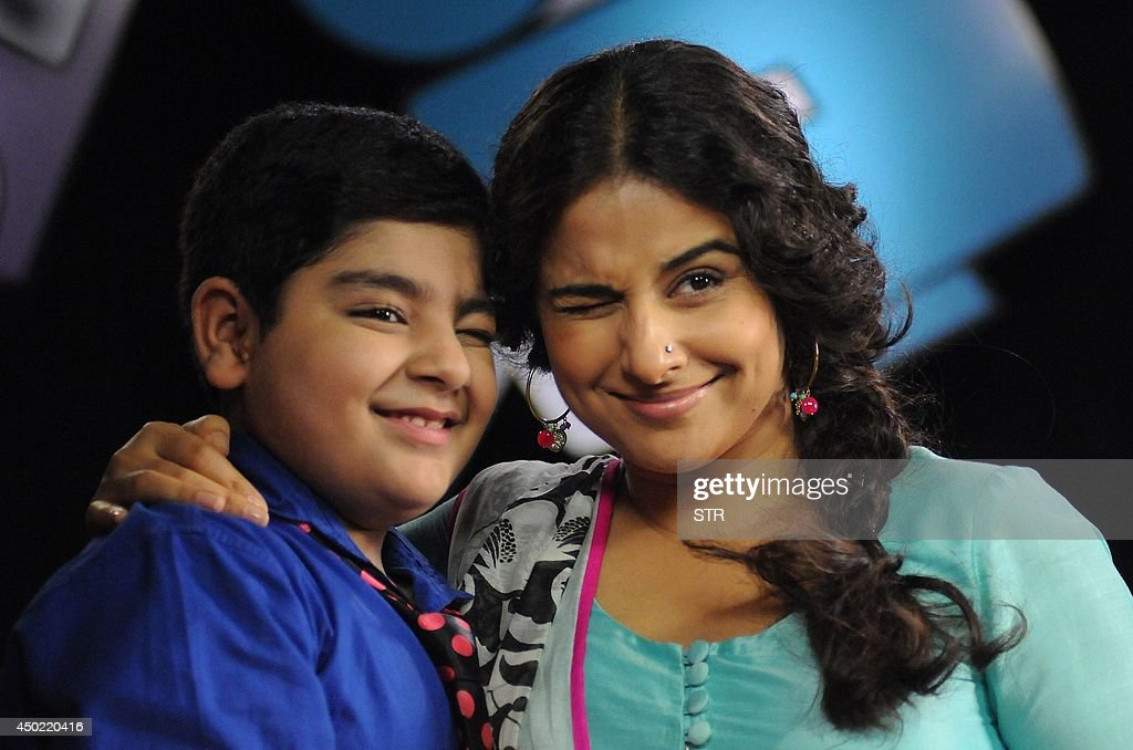 Indian Bollywood film actress Vidya Balan poses with a child