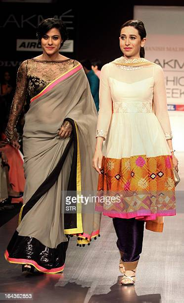 Indian Bollywood film actresses Kajol Devgan and Karishma Kapoor showcase creations by designer Manish Malhotra during a fashion show on the first...