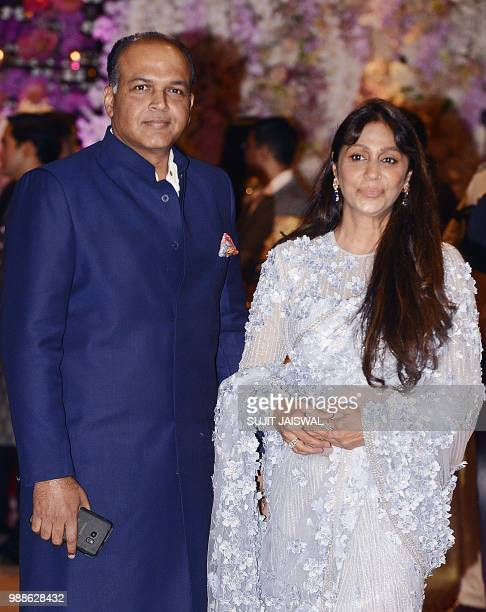 Indian Bollywood film director Ashutosh Gowariker poses for a picture with wife Sunita as they attend the preengagement party of India's richest man...