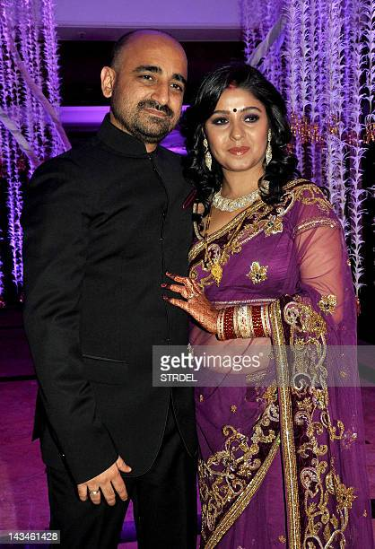 Indian Bollywood playback singer Sunidhi Chauhan poses with her husband musician Hitesh Sonik during their wedding reception in Mumbai on April 26...