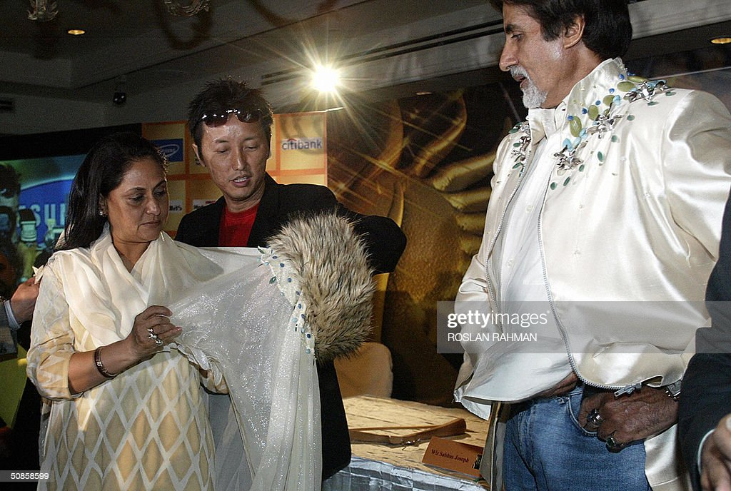 Indian Bollywood star Amitabh Bachchan (R) looks on while his wife (L) is presented with a sash during a press conference to mark the 5th International Indian Film Academy (IIFA) Award, in Singapore 20 May 2004.