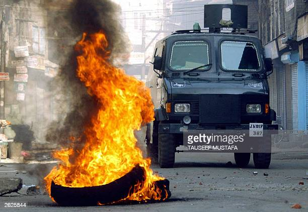 Indian border security force armoured vehicle drives by burning tyres 22 October 2003 during a protest against the arrest of influencial...